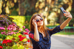 Girl in sunglasses making a self-portrait on phone. Selfie Stock Photography