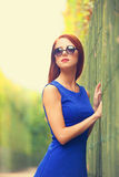 Girl in sunglasses near fence Royalty Free Stock Photography