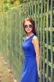 Girl in sunglasses near fence Stock Photo