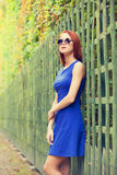 Girl in sunglasses near fence Royalty Free Stock Images