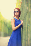 Girl in sunglasses near fence Royalty Free Stock Image