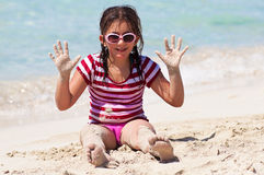 Girl with sunglasses playing on a beach Royalty Free Stock Photo
