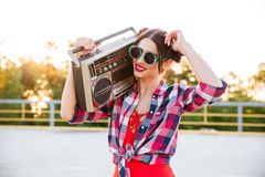 Girl in sunglasses and red swimsuit holding old record player Royalty Free Stock Images