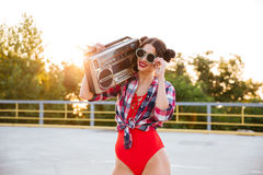 Girl in sunglasses and red swimsuit holding old record player Royalty Free Stock Photos