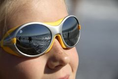Girl with sunglasses (reflecting the beach) Stock Image
