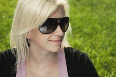 Girl with sunglasses sitting on the grass Stock Image