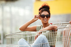 Girl in sunglasses sitting inside a shopping trolley outdoors Stock Photography