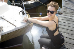 Girl in sunglasses sitting on a pier near the boat in. Beautiful girl in sunglasses sitting on a pier near the boat in the sunlight Stock Images
