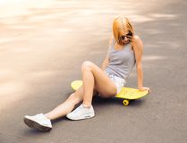 Girl in sunglasses sitting on skateboard outdoors Royalty Free Stock Images