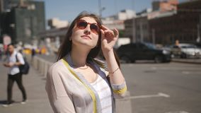 The girl standing at the road waiting for the arrival of a taxi. The girl with sunglasses standing at the road waiting for the arrival of a taxi stock footage