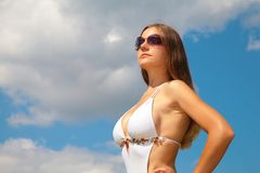 Girl in sunglasses in swimsuit against sky stock images