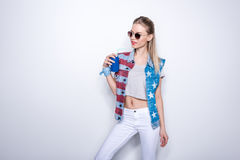 Girl in sunglasses wearing denim vest with stars and stripes and drinking soda from aluminum can Stock Images