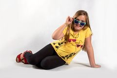 Girl in sunglasses on a white background. Cheerful girl in sun glasses and yellow shirt on white background Stock Photography