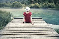 Girl with sunglasses and white hat sitting and enjoying on a wooden pier. By the turquoise blue lake covered with light fog, Zelenci, Slovenia stock photos