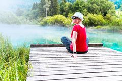 Girl with sunglasses and white hat sitting and enjoying on a wooden pier stock images