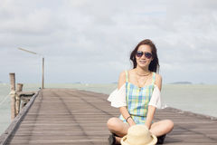 Girl in sunglasses on wood bridge and sea background Stock Photos