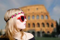 Girl in sunglasses and wreath on Coliseum blurred Royalty Free Stock Image