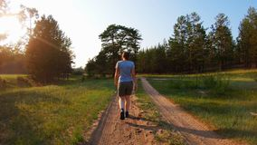 Girl in the sunlight walking on a country road at sunset. Rear view stock footage