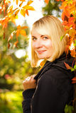 Girl at sunny autumn day. Beautiful smiling blond girl at sunny autumn day Royalty Free Stock Photos