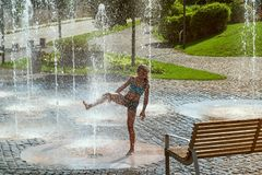 Girl on a sunny warm day playing outside in a water fountain. Girl happily in shallow clean water on of city fountain on warm royalty free stock photography