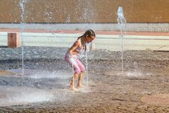 Girl on a sunny warm day playing outside in a water fountain. Girl happily in shallow clean water on of city fountain on warm royalty free stock image