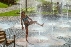 Girl on a sunny warm day playing outside in a water fountain. Girl happily in shallow clean water on of city fountain on royalty free stock photography