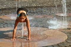 Girl on a sunny warm day playing outside in a water fountain. Girl happily in shallow clean water on of city fountain on warm royalty free stock images