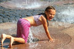 Girl on a sunny warm day playing outside in a water fountain. Girl happily in shallow clean water on of city fountain on warm stock photo