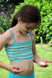 Girl and sunscreen. Girl putting suncream on her skin before sunbathing in the garden Stock Images