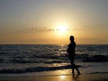 Girl in the sunset. Silhouette of a pregnant girl on the background of a calm sea at sunset Stock Photo