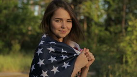 Girl at sunset with American flag in hands. Beautiful woman with the American flag at sunset in the forest stock video footage