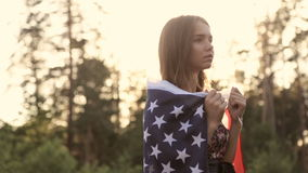 Girl at sunset with American flag in hands. Beautiful woman with the American flag at sunset in the forest
