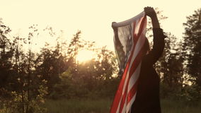Girl at sunset with American flag in hands. Beautiful woman with the American flag at sunset in the forest stock footage