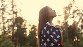 Girl at sunset with American flag in hands. Beautiful woman with the American flag at sunset in the forest stock video