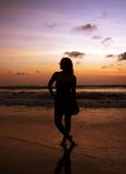 Girl on the sunset beach Stock Photos