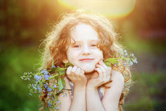 Girl at sunset with blue flowers in her hands. Background toned Royalty Free Stock Photos