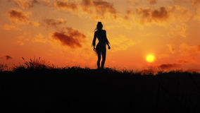 Girl On The Sunset Hill. Girl on top of a hill covered with vegetation enjoying the glorious sunset Stock Photos
