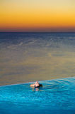 Girl in Sunset infinity pool. A beautiful young model floating in an infinity pool at sunset Royalty Free Stock Images