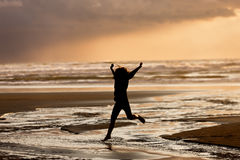 Girl at sunset jumps into water. Stock Photos