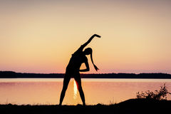 Girl at sunset by the lake Royalty Free Stock Photography
