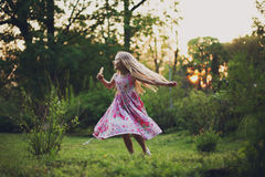 Girl and sunset light. Little girl in sunset light in green park playing Royalty Free Stock Images