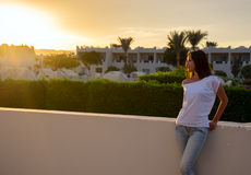 Girl and sunset. Girl and sunset! The girl looks at the sunset. The sun sets behind the building Royalty Free Stock Photos