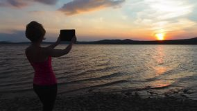 The girl, a sunset, a mountain lake, the phone stock video