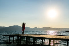 Girl at sunset on the pier. Girl at sunset in a pink dress on a pier Royalty Free Stock Photo