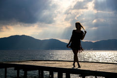 Girl at sunset on the pier. Girl at sunset walking on a pier Royalty Free Stock Image