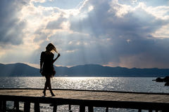 Girl at sunset on the pier. Girl at sunset walking on a pier Royalty Free Stock Photo