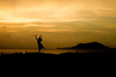 Girl on Sunset rock -  Silhouette Royalty Free Stock Photo