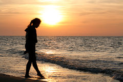 Girl at sunset. Girl in summer standing and looking to a sea Royalty Free Stock Photography