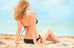 Girl with suntan lotion at the beach Royalty Free Stock Images
