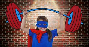 Girl in superhero costume pretending to lift weights against wooden background Stock Photo